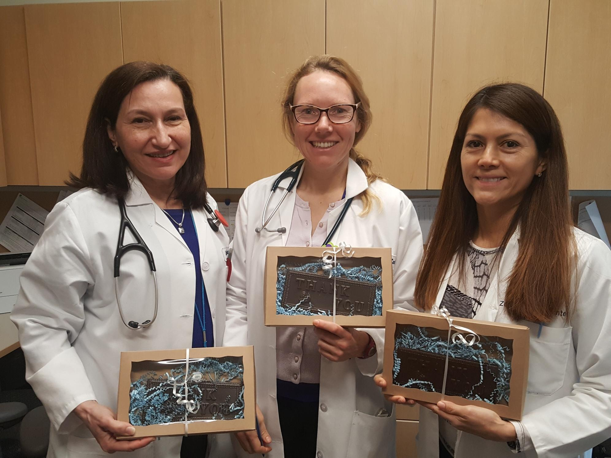 Photo of three Zufall Health medical providers holding small gifts of appreciation