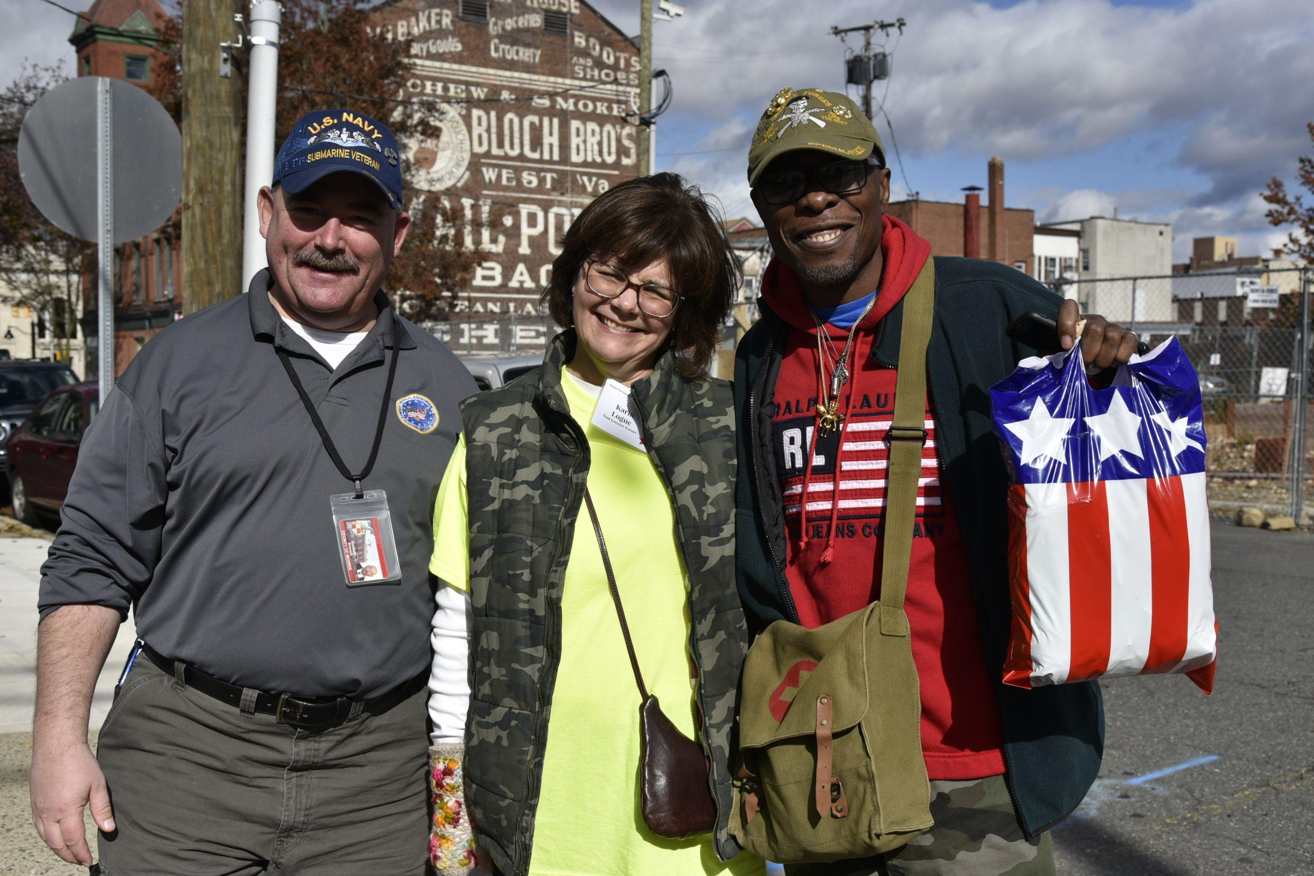 A volunteer at the Smiles for Our Heroes events poses with two veterans.