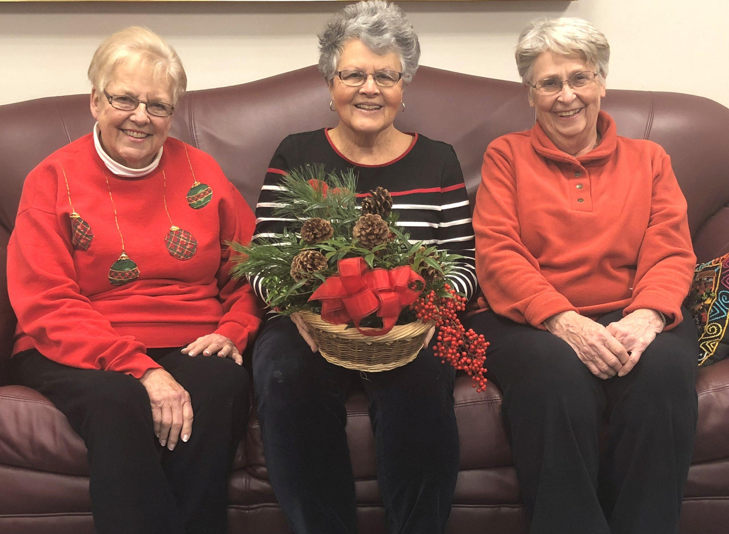 Photo of three members of the Bridgewater Garden Club sitting on a couch holding a holiday arrangement.