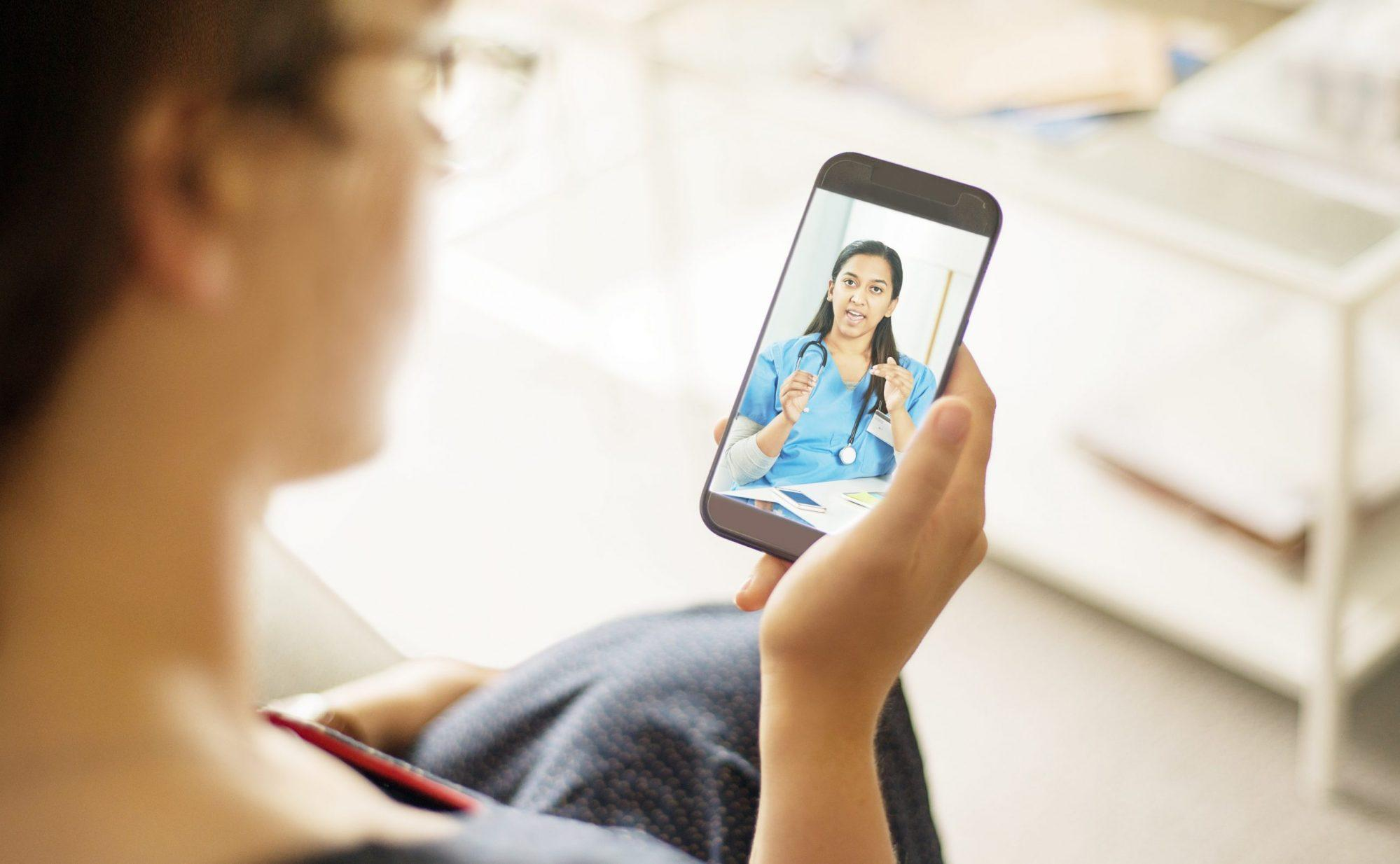 Photo of a Telemedicine Patient speaking with a medical Provider on Cell Phone. The provider is wearing blue scrubs.