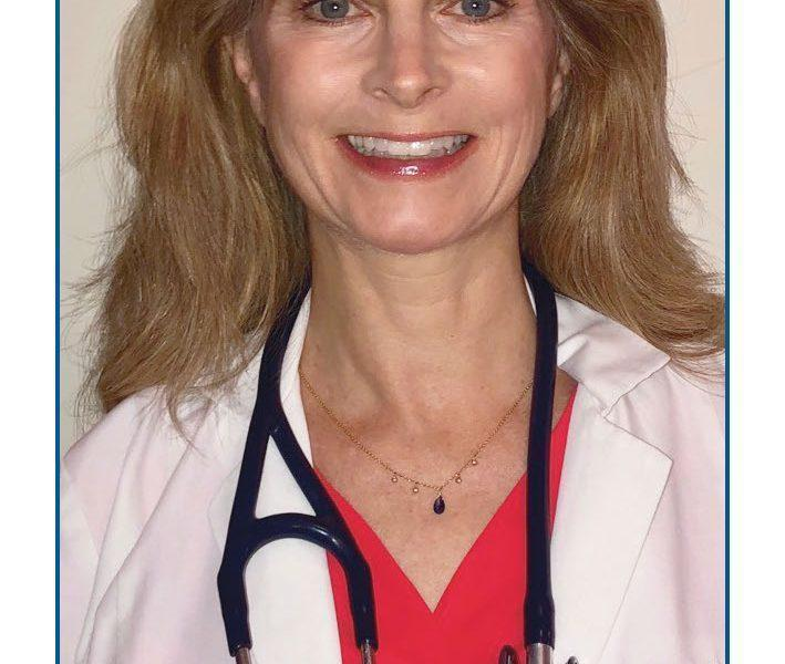 Headshot of Dr. Loris Jarvis. Dr. stares straight and smiles. She has long dark blond hair and wears a red shirt, white lab coat and a stethoscope around her neck.