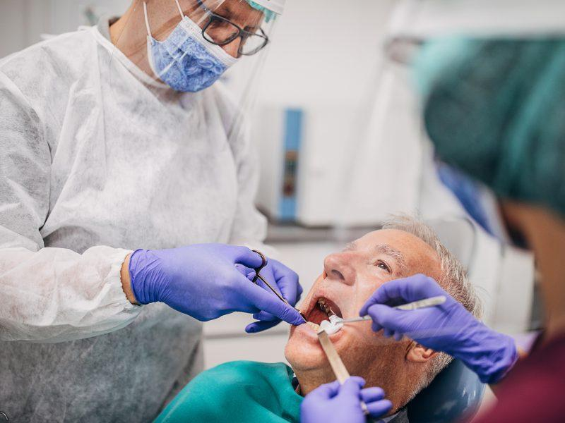 Male dentist and his female assistant wearing a protective gowns, eyewear protection, protective face masks and gloves while working on the teeth of an elderly male patient
